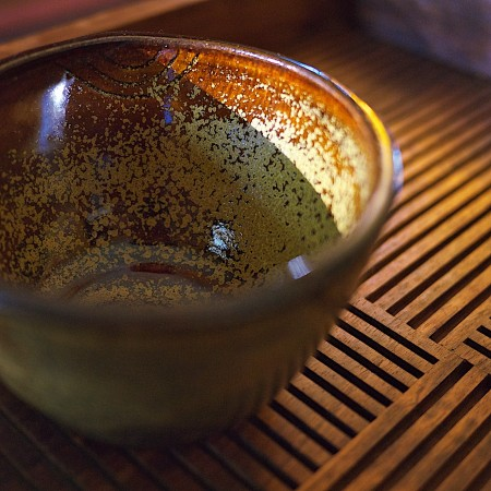 Ceramic cup on wooden tray.