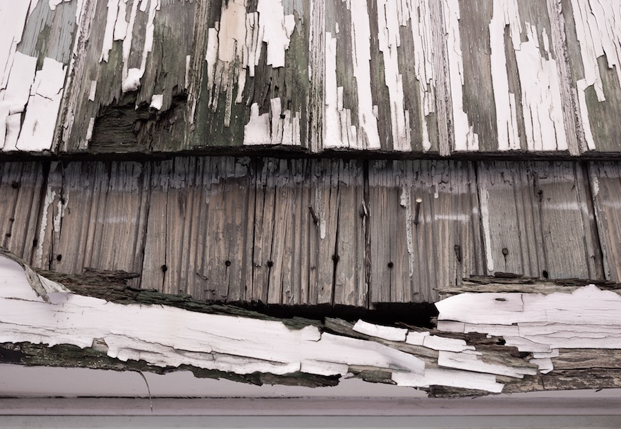 Peeling paint & exposed wood.