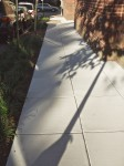 Shadows and reflections on sidewalk pavement.