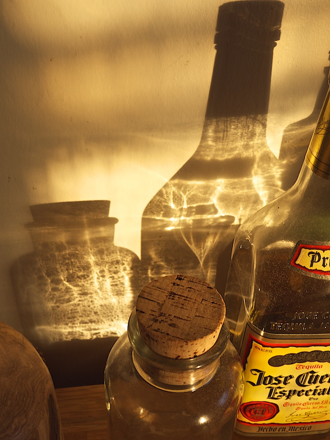 Late afternoon light refracted through glass bottles.