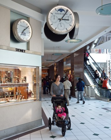 Woman pushing stroller in mall.