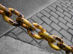 Rusty yellow chain against pavement