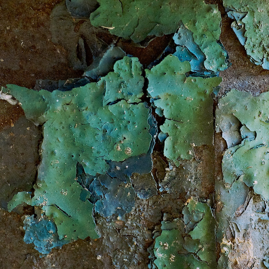Flaking layers of blue and green paint on a fire hydrant.