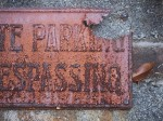 Rusted no trespassing sign.