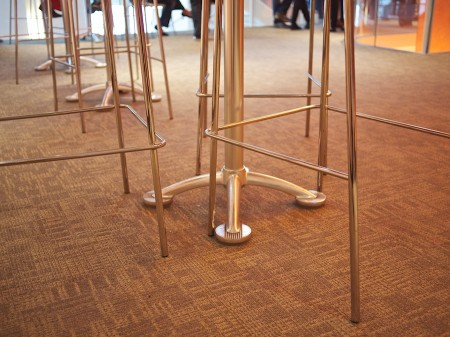 Table and chair legs, people's feet in background.
