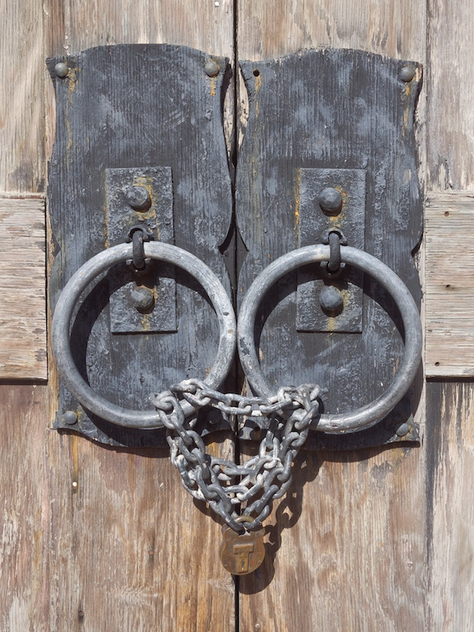 Old door knobs and locked chain.