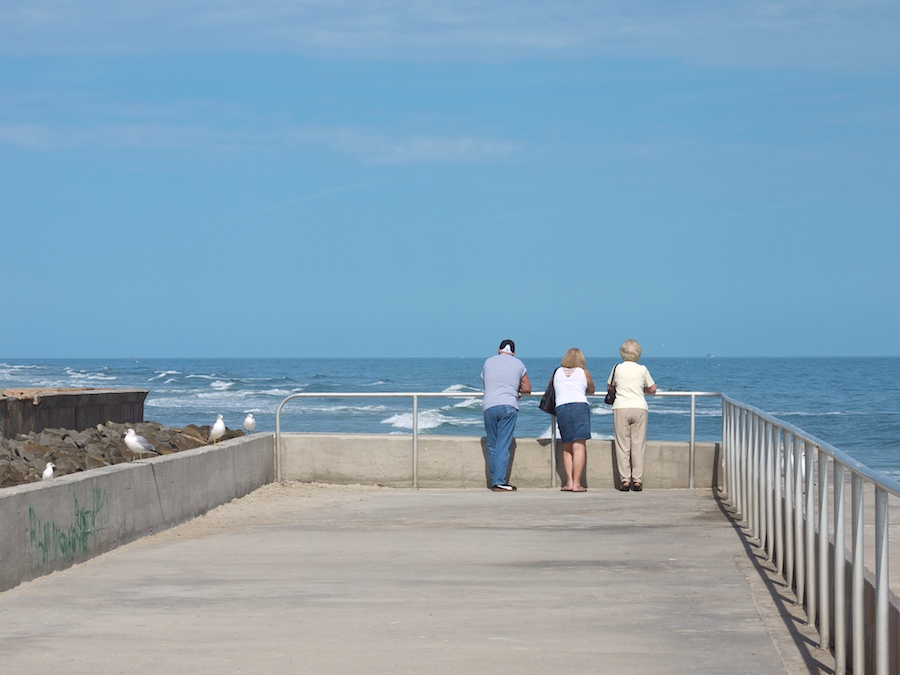 Three people contemplate the ocean, St. Augustine Beach, FL