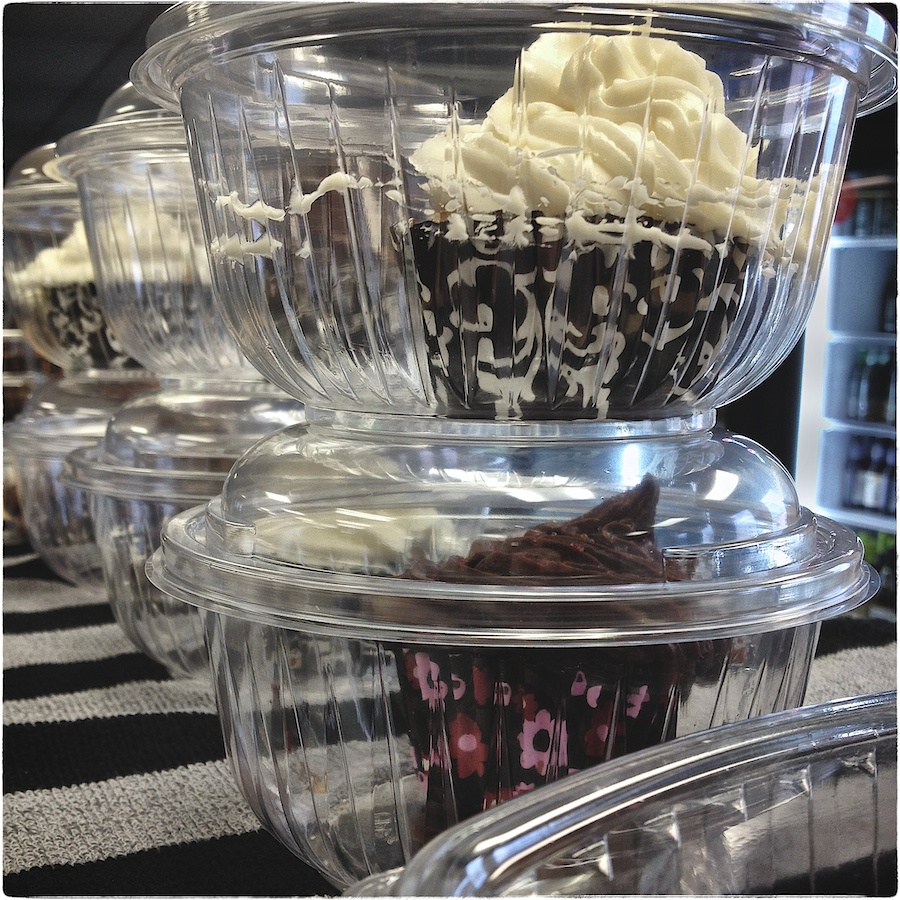 Cupcakes in plastic containers on bar towel.