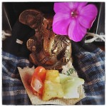 Little Ganesha with flower and food offerings.