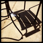 Outdoor furniture shadows on sidewalk.