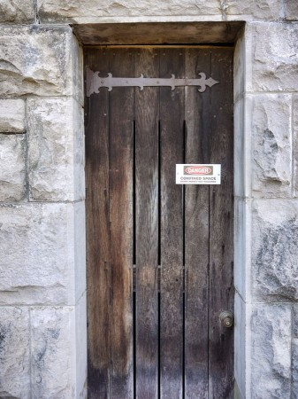 Narrow wooden door in stone wall with danger sign.