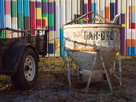 Vehicle, rusted hopper, painted siding.