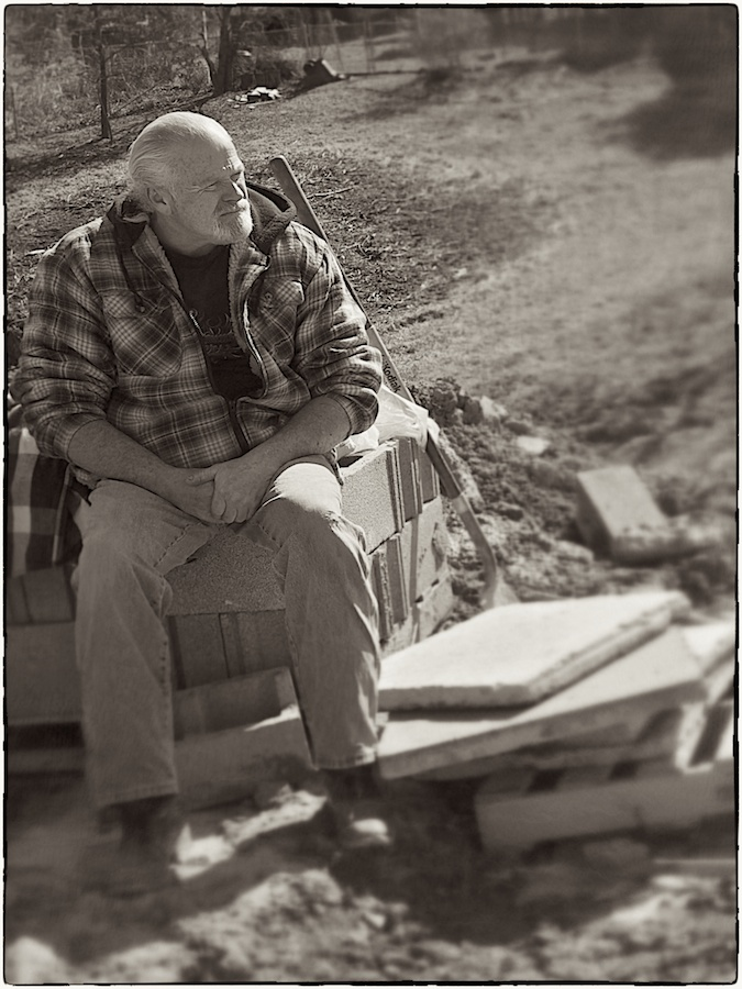 Construction worker sitting on work materials.