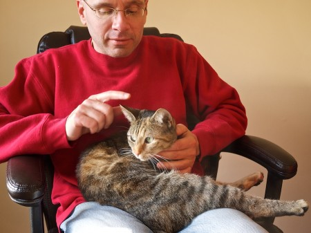 Bob pets the cat in his lap with one finger.