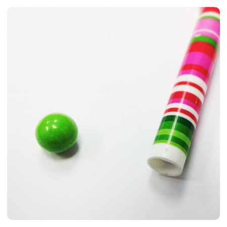 Striped pen and green candy.