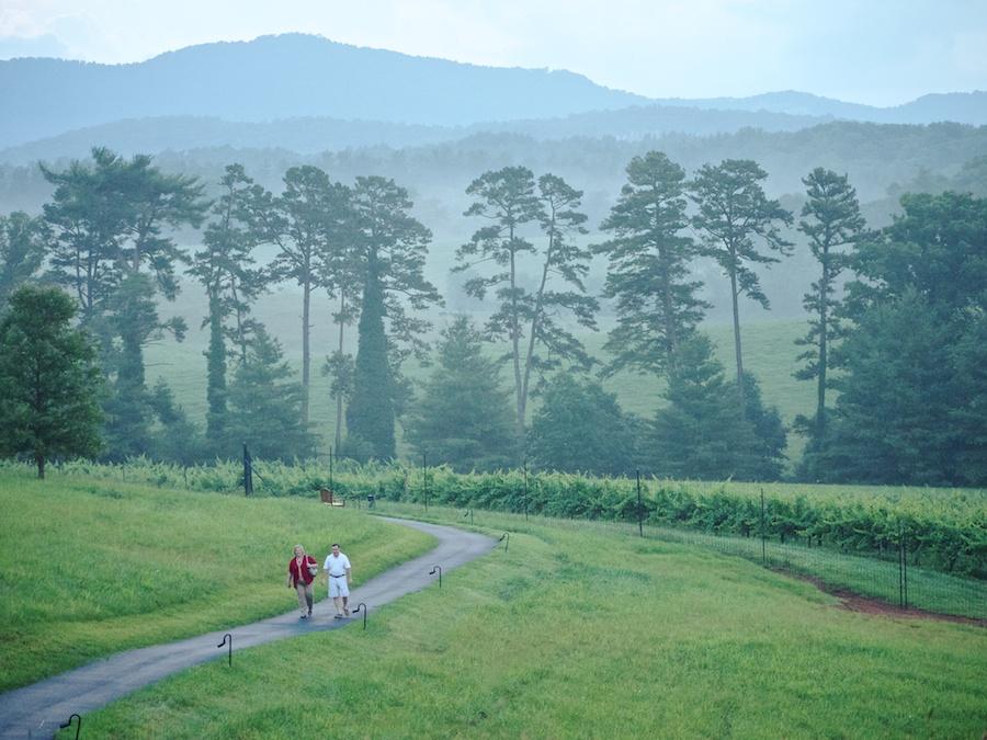 Couple walks on path near Inn on Biltmore Estate, Asheville, NC