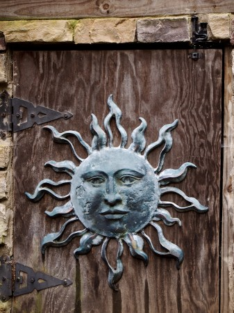 Metal sun on wooden door.