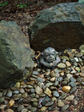 Small troll sculpture in rock setting at Wamboldtopia.