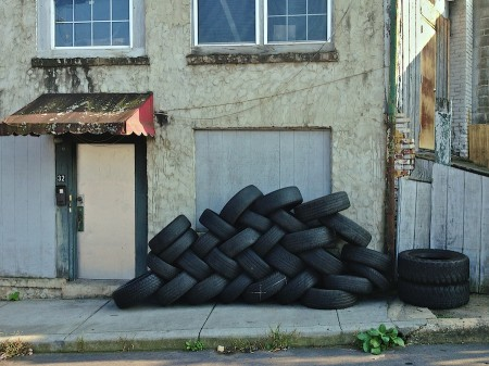 Tires piled outside neglected building.