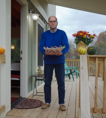 Man on porch holding Halloween candy bowl.