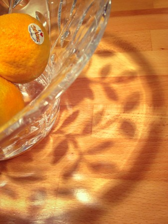 Oranges in cut glass bowl with shadows.