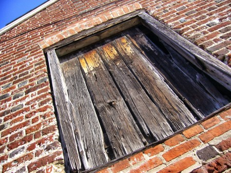 Boarded up window in old brick building.