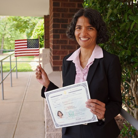 Naturalized citizen with certificate and flag.