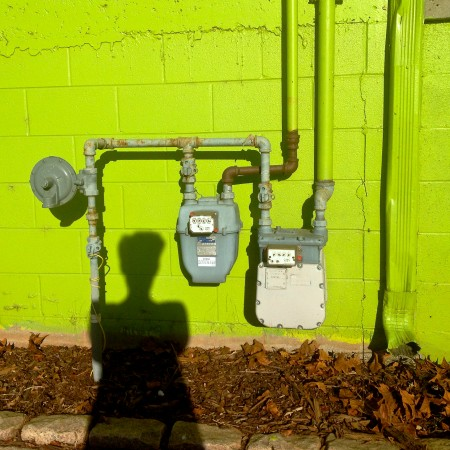 Human Shadow and Utility meters on acid green wall.